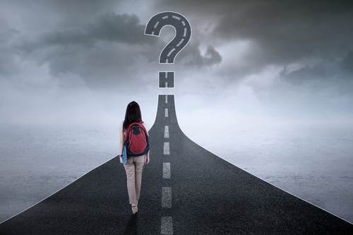Female student walking on the street while carrying backpack with a question mark on the end